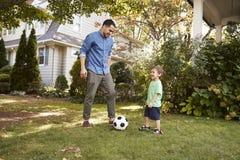 De Tuin van vaderplaying soccer in met Zoon stock afbeelding