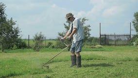 De tuinman snijdt het gras met de snoeischaar van het gazonkoord stock footage