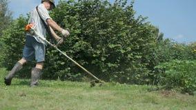 De tuinman snijdt het gras in openlucht met een grasmaaier stock video