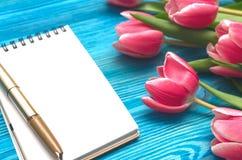 De tulpenbloemen en de lege nota vullen document pagina op houten achtergrond met exemplaarruimte op het concept van de vrouwenda Royalty-vrije Stock Foto's