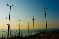 De turbineslandbouwbedrijf van de wind met een zonsondergang Stock Afbeelding