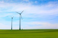 De turbineslandbouwbedrijf van de wind op gebied over bewolkte hemel Stock Foto