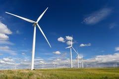 De turbineswit van het windlandbouwbedrijf op het groene gras van het heuvelcontrast en blauwe hemel, wa Stock Foto