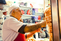 De Turkse mens kookt en verkoopt kebab Stock Foto's
