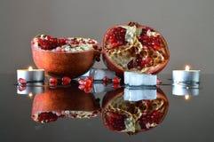 De två halvorna av en granatäpple, en is och stearinljus royaltyfri bild