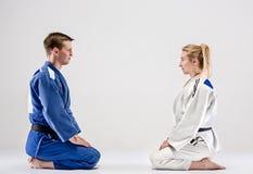 De två judokaskämparna som poserar på grå färger arkivbild