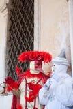 De två karnevalmaskeringarna som diskuterar nära porten Royaltyfri Bild