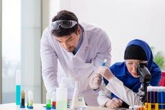 De två kemisterna som arbetar i labbet arkivfoton