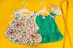 De två klänningarna för lilla flickan på en gul bakgrund fotografering för bildbyråer