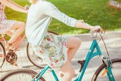 De två unga flickorna med cyklar parkerar in royaltyfri bild