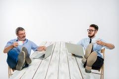De två affärsmännen med ben över tabellen som arbetar på bärbara datorer Arkivbilder