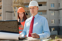 De twee arbeiderswerken aangaande het bouwterrein Royalty-vrije Stock Afbeelding