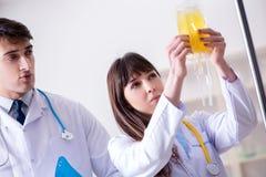De twee artsen die plasma en bloedtransfusie bespreken stock foto