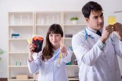 De twee artsen die plasma en bloedtransfusie bespreken stock foto's