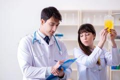 De twee artsen die plasma en bloedtransfusie bespreken stock fotografie
