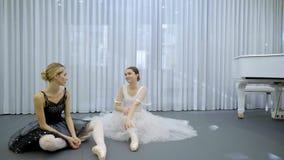 De twee ballerina's zitten op de vloer en spreken tijdens de onderbreking in balletklasse stock videobeelden