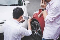 De twee bestuurdersmens die na een het ongevallenbotsing van het autoverkeer debatteren en tot telefoongesprek maken aan Verzeker royalty-vrije stock afbeeldingen