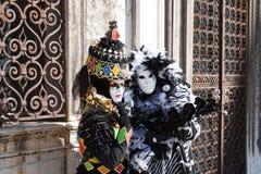 De twee Carnaval-kostuums dichtbij de ijzerpoorten Stock Foto's