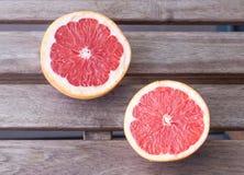 De twee grapefruithelften op een houten achtergrond Royalty-vrije Stock Fotografie