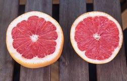 De twee grapefruithelften op een houten achtergrond Stock Fotografie