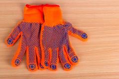 De twee handschoenen leggen op een vlakke houten oppervlakte stock afbeelding