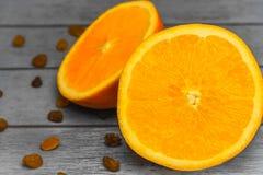 De twee helften sinaasappel en rozijnen Stock Foto