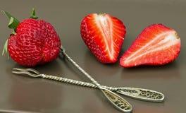 de twee helften van aardbeien en een bes met vorken Stock Foto