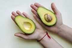 De twee helften van avocado op kinderen` s palmen Royalty-vrije Stock Foto