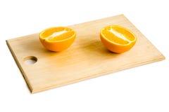 De twee helften van sinaasappel op houten plaat Stock Afbeeldingen