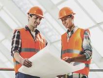 De twee Industriële Ingenieurswerken met Blauwdruk royalty-vrije stock foto