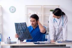 De twee jonge artsen die in de kliniek werken royalty-vrije stock afbeelding