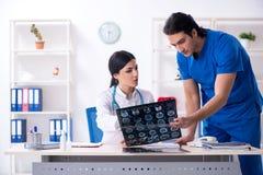 De twee jonge artsen die in de kliniek werken royalty-vrije stock afbeeldingen