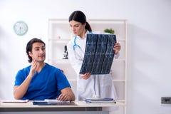 De twee jonge artsen die in de kliniek werken stock fotografie
