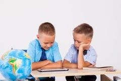 De twee jongens bekijken Internet-Tabletschool stock foto