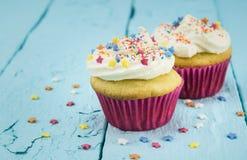 De twee koppencakes met ster bestrooit op blauwe lijst - achtergrond Royalty-vrije Stock Foto