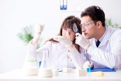 De twee laboratorium arts het testen voedingsmiddelen royalty-vrije stock afbeelding