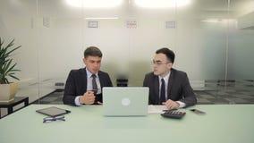 De twee mannelijke managers bespreken het rapport in mede-werkt ruimte met glasmuur stock videobeelden