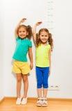 De twee meisjesgreep overhandigt hand dichtbij schaal op muur stock foto