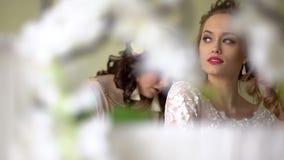 De twee meisjeshulp kleedt de bruid Iedereen glimlacht, zijn de meisjes verfraaid met bloemen stock video
