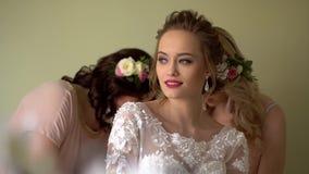 De twee meisjeshulp kleedt de bruid Iedereen glimlacht, zijn de meisjes verfraaid met bloemen stock videobeelden