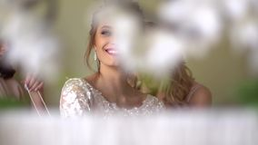 De twee meisjeshulp kleedt de bruid Iedereen glimlacht, zijn de meisjes verfraaid met bloemen stock footage