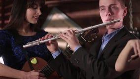 De twee mensenmusicus reproduceert muziek Een kerel in een jasje en een overhemd speelt de fluit, en een mooi brunette in het bla stock footage