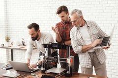 De twee mensenopstelling een 3d printer, een bejaarde houdt laptop in zijn handen en let op het proces Royalty-vrije Stock Afbeelding