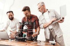 De twee mensenopstelling een 3d printer, een bejaarde houdt laptop in zijn handen en let op het proces Royalty-vrije Stock Afbeeldingen