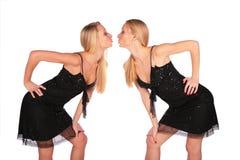 De tweeling meisjes neigen van aangezicht tot aangezicht aan elkaar Stock Foto