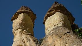 De tweeling recht-bedekte bovenkanten van de rotsvorming tegen een blauwe hemel stock videobeelden