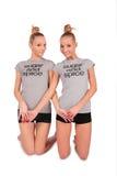 De tweeling tribunes van sportmeisjes op knieën Stock Afbeeldingen