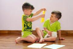 De tweelingbroers spelen met document Royalty-vrije Stock Afbeelding