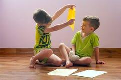 De tweelingbroers spelen met document Stock Fotografie