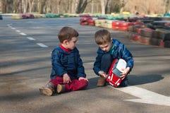 De tweelingbroers spelen met een stuk speelgoed auto Stock Afbeeldingen